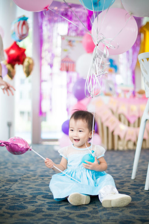 Baby girl at her birthday party with helium balloons in background