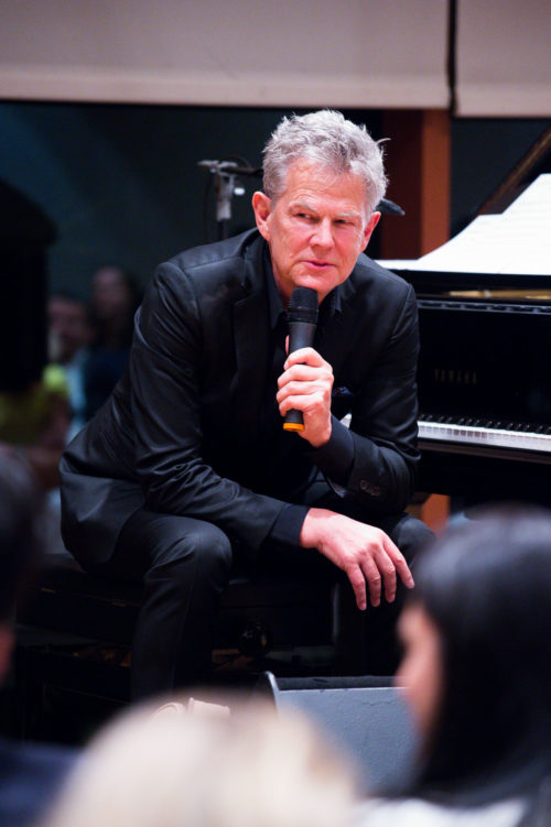 Painist speaking to audience at a concert